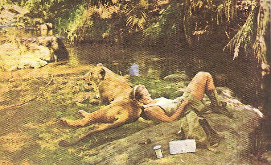 Joy Adamson resting on Elsa the Lion by her favorite river