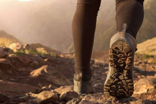 close up of a hiker's shoe covered in dirt on a mountain