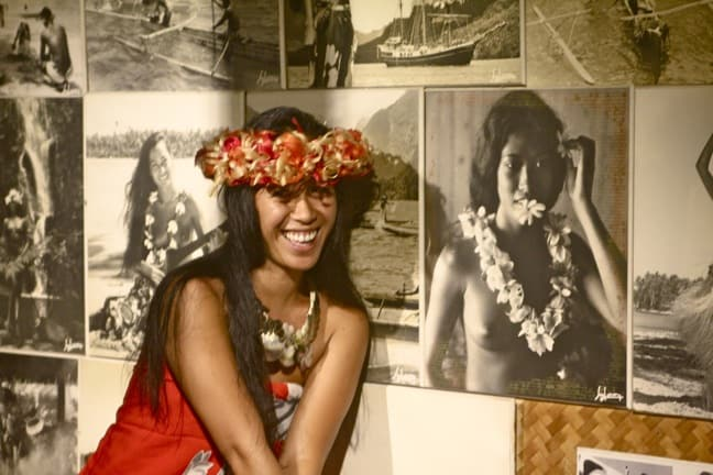 Moorea Tiki Village Guide Poses Next to Classic Tahitian Photos by Sylvain
