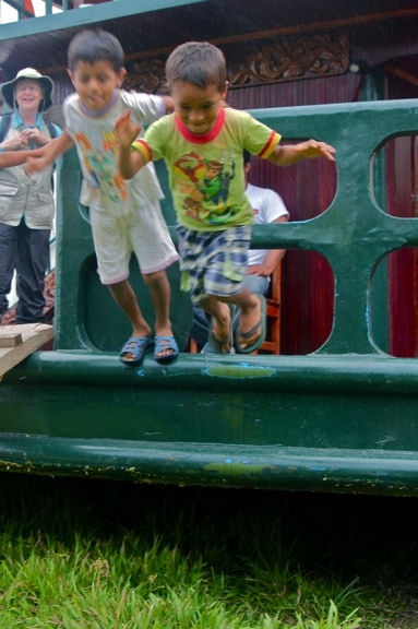 Boys jump from a tourist boat in Nueva York village, in Peru's Amazon